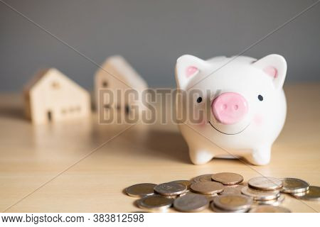 Selective Focus At The Face Of Piggy Bank. Piggy Bank On Wooden Table With Blurred Coins And House M