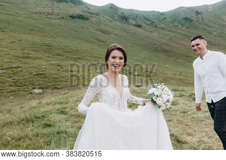 Bride With A Bouquet Of Flowers With Her Fiance Against The Backdrop Of The Mountains