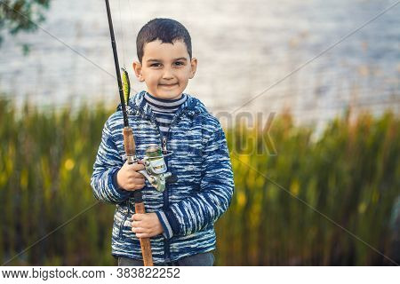 Cute Boy Catches Fish On A Summer Lake.