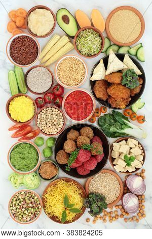 Vegan super food for a healthy planet with foods high in antioxidants, protein, omega 3, dietary fibre, anthocyanins, smart carbs, vitamins & minerals. Plant based ethical eating concept. On marble.