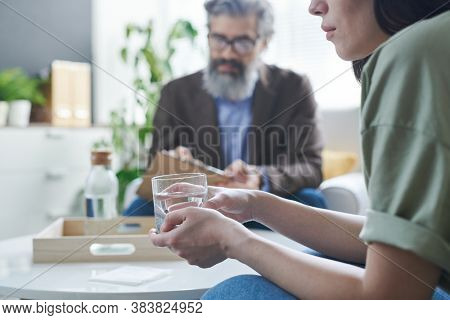 Low-spirited woman holding glass of water trying to calm down during therapy session at psychologist office