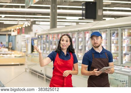 Two hypermarket merchandise specialists wearing uniform walking along aisles discussing some issues, copy space