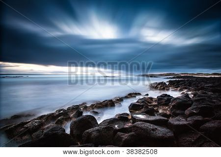 Dramatic ocean sunset with rolling cloud and wave