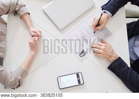 Directly frome above shot of unrecognizable woman sitting in front of man with CV paper having job interview