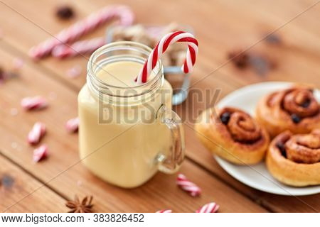 christmas and seasonal drinks concept - eggnog in glass mug with candy cane decoration, cinnamon buns and aromatic spices on wooden background