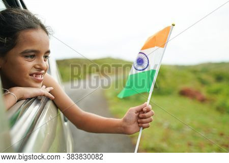 Happy Cheerful Young Girl Kid Holding Indian Flag Out Of In Moving Car Window - Concept Of Patriotis