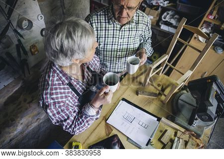 Senior Couple Pausing For Coffee In Their Carpentry Workshop