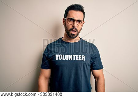Handsome man with beard wearing t-shirt with volunteer message over white background In shock face, looking skeptical and sarcastic, surprised with open mouth