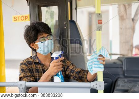 Young Man In Medical Mask Disinfecting Or Sanitizing Bus By Using Alcohol Disinfectant Spray To Prot