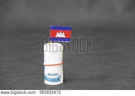 Rolled Banknote Money One Thousand Cambodian Riel And Stick With Mini Cambodia Flag On Dark Grey Flo