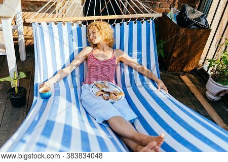 Carefree Blond Middle Age Woman Drinking Tea, Having Bbreakfast, Relaxing In A Hammock During Summer