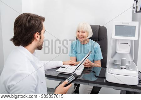 Smiling Senior Woman Have Consultation With Her Optometrist For An Eye Check-up. Eye Exam And Vision