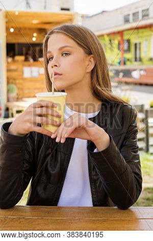 A Beautiful Young Girl Drinks Coffee From An Eco-friendly Cup Through An Eco-tube At A Table In A St