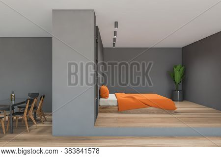 Interior Of Modern Bedroom With Gray Walls, Wooden Floor, King Size Bed With Orange Blanket And Dini