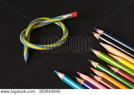 Flexible Pencil And A Set Of Colored Pencils On A Dark Background. Selective Focus