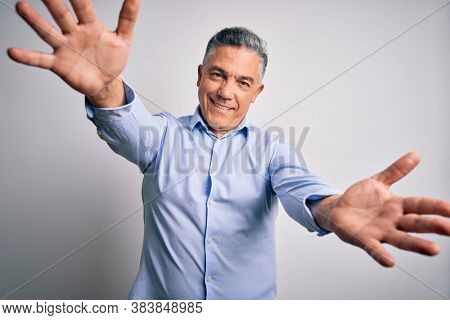 Middle age handsome grey-haired business man wearing elegant shirt over white background looking at the camera smiling with open arms for hug. Cheerful expression embracing happiness.
