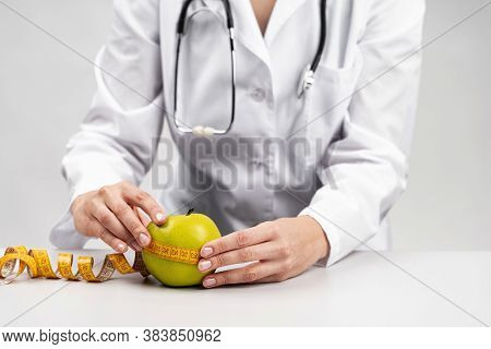 Nutritionist woman measuring apple. Health care concept.