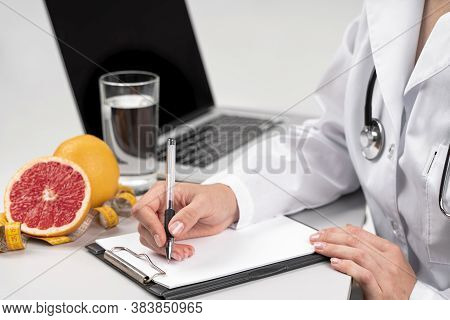 Nutritionist writing clipboard. Health care concept. Gray back ground.
