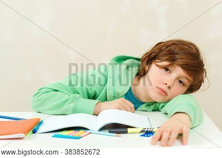 Tired Kid Sitting At The Desk With Many Book. Sad Schoolboy Doing Homework. Tired Schoolboy Sitting
