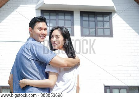 Asian Male And Female Couples Stand, Hug, And Smile Happily In Front Of The New House. The Concept O