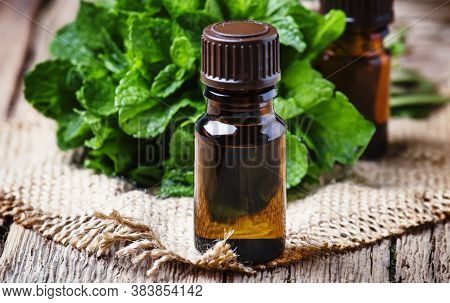 Essential Oil Of Peppermint In A Small Brown Bottle With Fresh Green Mint, Rustic Style, Vintage Woo