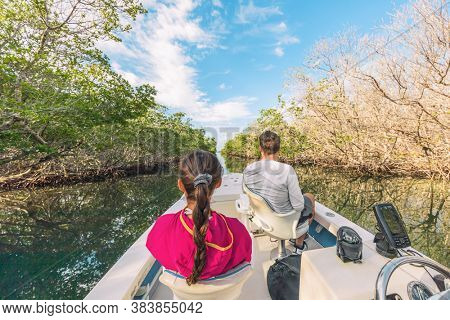 Boat tour in the Everglades, Florida, USA. Popular tourist attraction from the Keys, Miami ,Orlando. People on guided ride for wildife sighthing of alligators, wetlands.