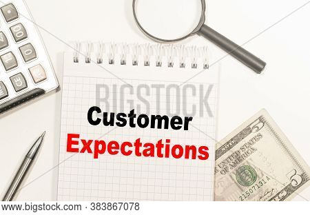 Text Customer Expectations Written On Notepad With Calculator, Pensil, Magnifier And Dollars. Busine