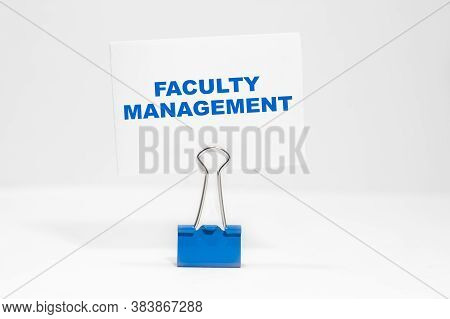 Faculty Management Nscription On A White Business Card On A White Endless Background In A Blue Clip.