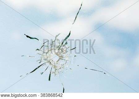 Bullet Hole In Glass Against The Background Of The Sky, Close-up