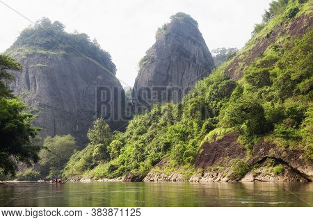 Bamboo Rafts Traveling Down Nine Bend River In Wuyishan, Fujian Province China On A Hazy Summer Day.