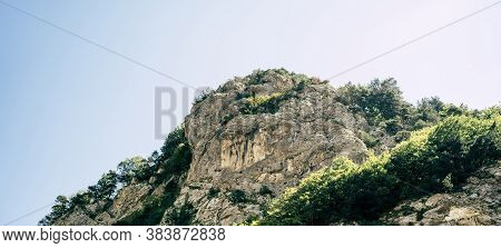Mountain Peaks Against Cloudy Sky. Peaks Of Magnificent Rocks Located Against Bright Cloudy Sky On S