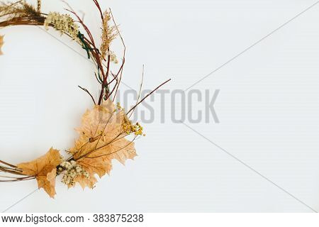 Handmade Rustic Autumn Wreath On White Wall. Rural Seasonal Wreath Made Of Autumn Leaves, Twigs And