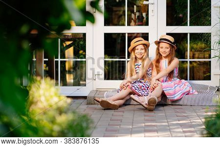 Two Little Girls, Sisters In Straw Hats Sit On The Doorstep Of The House Near The Glass Door In The