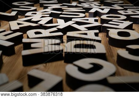 Heap of wooden letters are lying on the wooden board.