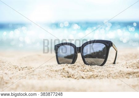 Sunglasses Placed On The Sand With Nature Reflection In Polarized Lenses And Blurred Sea View In The