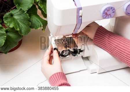 The Girl Is Threading The Needle Of A Sewing Machine. Close Plan. White Sewing Machine. Sewing Conte
