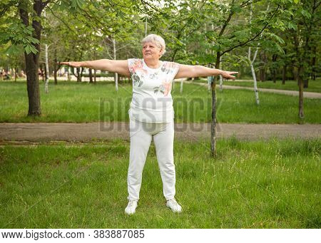 Optimistic Old Woman Exercising For Healthy Life In Open Air. Mature Woman Practicing Yoga. Funny Ol
