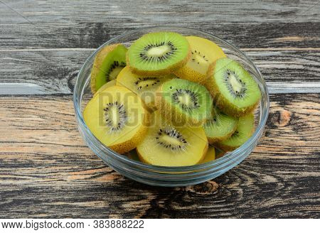 Raw Fresh Golden Yellow And Green Kiwi Fruit Slices In Glass Bowl On Table
