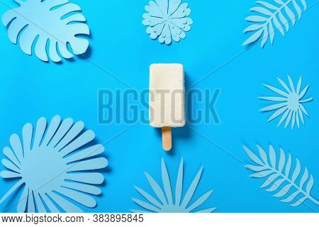 Top View Fresh Half Baked Cheese Flavor Popsicle On Blue With Hand Cut Flower And Leaves