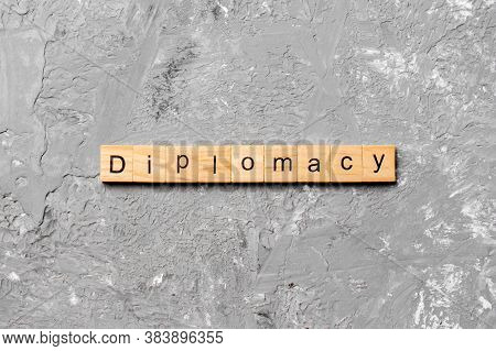 Diplomacy Word Written On Wood Block. Diplomacy Text On Cement Table For Your Desing, Concept
