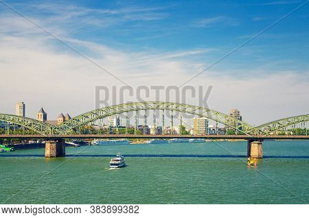 The Hohenzollern Bridge Or Hohenzollernbrucke Across Rhine River With Tourist Boat Sailing On Water,