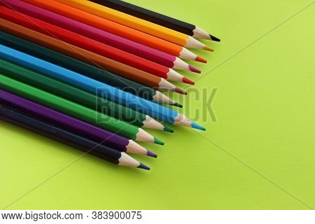 Colored Pencils On Yellow Background. Lots Of Different Colored Pencils. Pencils Are Very Sharp. Pen