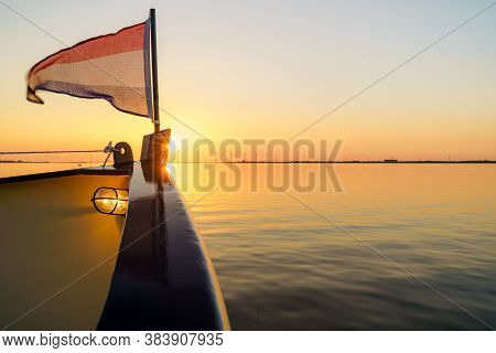Fore-deck Steel Boat With Dutch Flag During Sunset Cruise