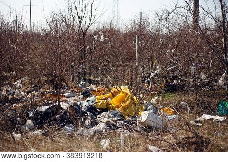 Horizontal View Of A Garbage, Plastic, Bags And Polyester Spread And Discarded In The Dry Grass In F