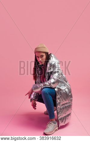 A Cool Woman In A Shiny Silver Down Jacket And A Knitted Hat Squatted Down, Studio Shot On A Pink Ba