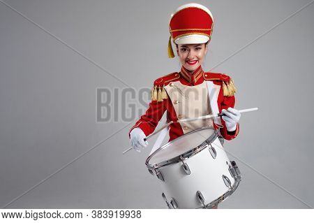 Cheerful Young Woman In A Red Cap And Uniform Plays A Drum. A Member Of The Festive Orchestra Plays