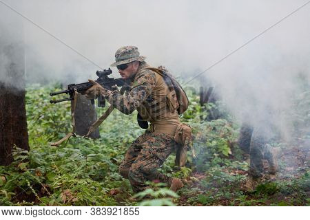 modern warfare soldier in action aiming at weapon  laser sight optics  in combat position while searching for a target in battle