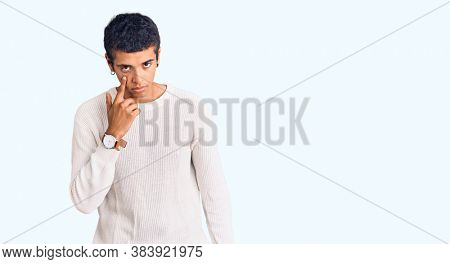 Young african amercian man wearing casual clothes pointing to the eye watching you gesture, suspicious expression