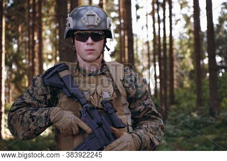 soldier portrait with  protective army tactical gear  and weapon in forest