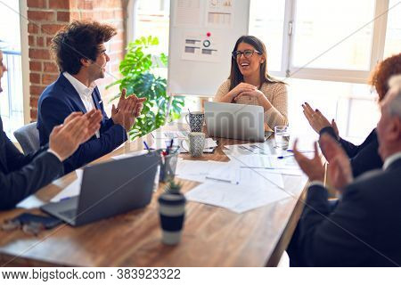 Group of business workers smiling happy and confident in a meeting. Working together looking at presentation using board and laptop applauding at the office.